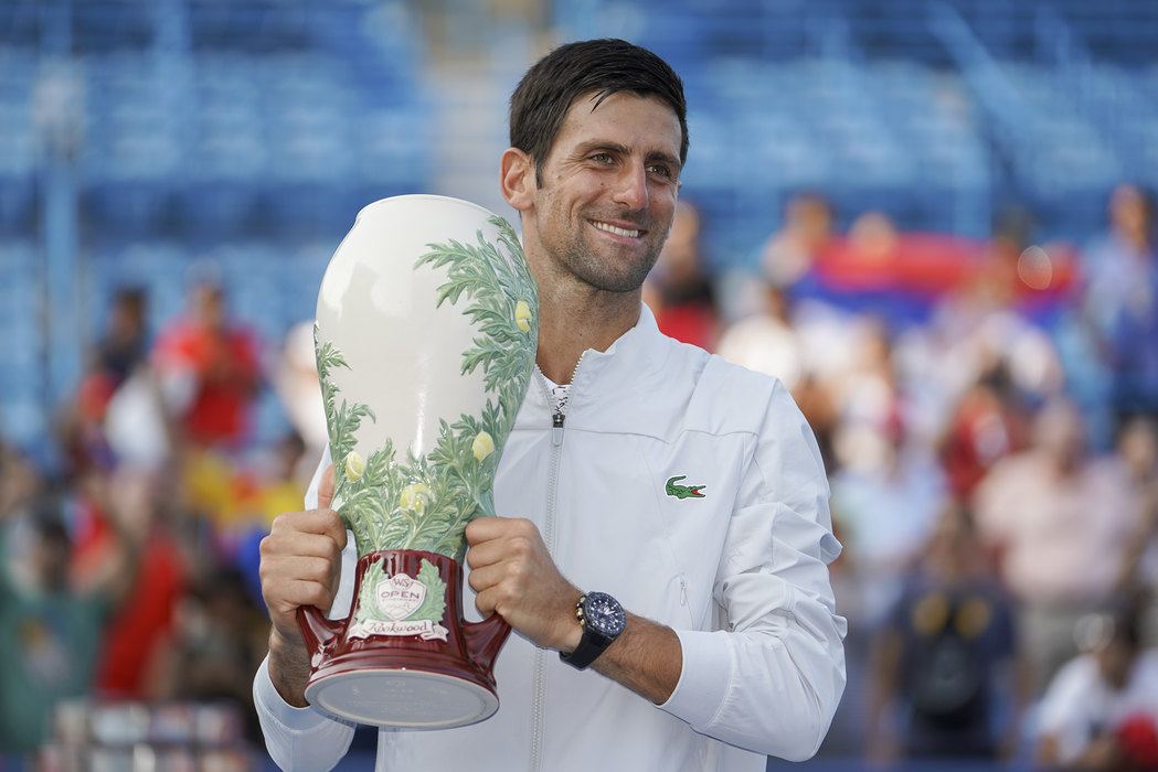 Novak Djokovic, of Serbia, holds the Rookwood Cup after defeating Roger Federer, of Switzerland, during the finals at the Western & Southern Open tennis tournament, Sunday, Aug. 19, 2018, in Mason, Ohio. (AP Photo/John Minchillo)